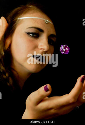A young female dressed as an elf with a polyhedral twenty sided die often used in role playing games. - Stock Photo