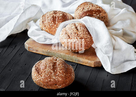 Wholemeal bread with seeds on wood kitchen board. - Stock Photo