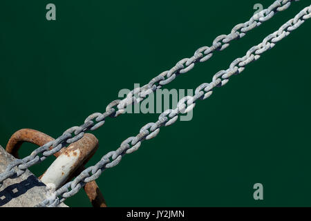 Detail of mooring chain anchored to dock, above the water. - Stock Photo