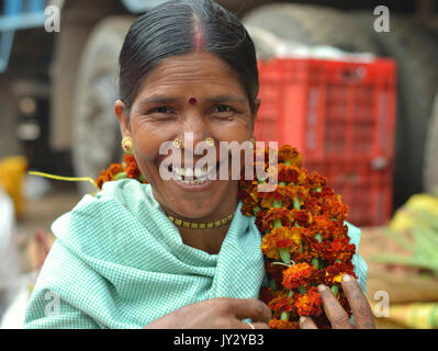 Closeup street portrait of a smiling and laughing mature Indian Adivasi market woman, carrying a flower garland - Stock Photo