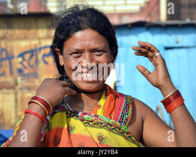 Closeup street portrait of a smiling and laughing mature Indian Adivasi woman, doing her hair with both hands (...and - Stock Photo