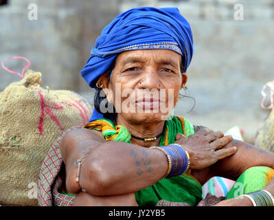 Closeup street portrait of an elderly Indian Adivasi market woman with blue headwrap and blue bangles. - Stock Photo