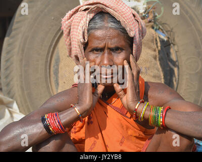 Closeup street portrait of an old Indian Adivasi market woman, resting her chin on her hands (...and showing her - Stock Photo