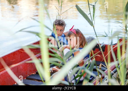 Family and friends summer vacation. Children ride on a boat outdoors. Boy with a girl riding on a boat on the lake - Stock Photo