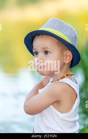 Portrait of a cute little boy with a hat, stands by the river and enjoy the beautiful and sunny day. Baby boy - Stock Photo
