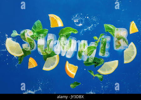 Ice cube lettering with frozen mint leaves, lemon slices and oranges on a blue background with water splashes. Text - Stock Photo