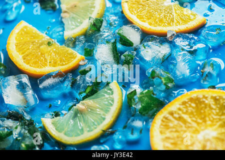 Close-up of sliced oranges and lemons on a blue background with ice cubes - Stock Photo