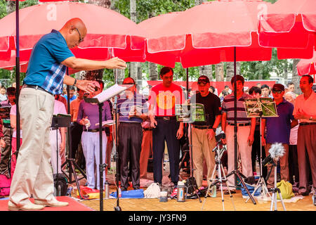 A group of retired Chinese men and women signing old songs together at Yu Yuan Tan park in Beijing, China - Stock Photo