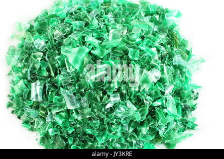 Small pieces of cut green plastic bottles on white paper - Stock Photo