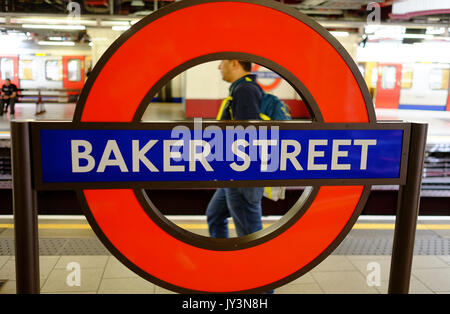 A passenger travels through Baker Street station in London  on the Metropolitan Line - Stock Photo