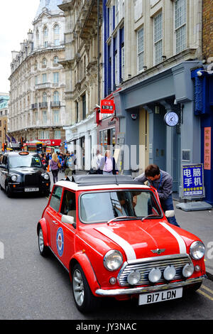A classic mini car with one of London's famous black taxis behind it, in Wardour Street, Soho near Chinatown, London - Stock Photo