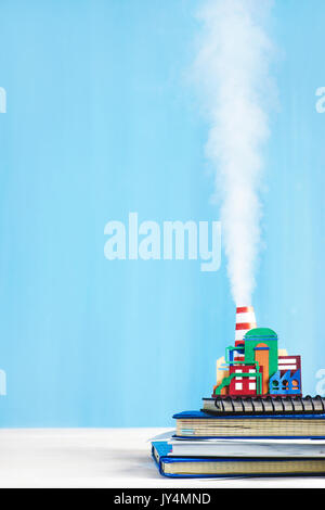 Steam engine papercraft. Still life with tiny industrial plant and rising smoke on a pastel blue background. - Stock Photo