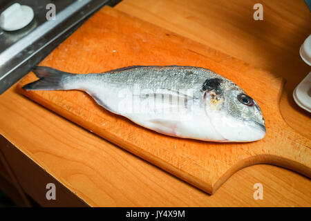 Detail of a raw bream fish on chopping board. - Stock Photo