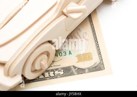 wooden car and US dollar isolated on white background. Concept for buying, renting, insurance, fuel, service and - Stock Photo