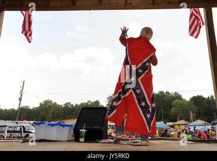 East Dublin, Georgia, USA. 11th Mar, 2008. Ronnie Mullis sports a Confederate Battle flag cape while performing - Stock Photo
