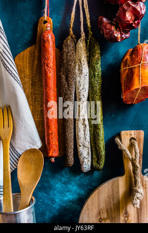 Assortment of traditional Spanish charcuterie meat sausages, kitchen utensils, towel, wood cutting board, rustic - Stock Photo