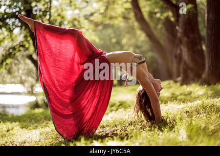 Fit young beautiful woman wearing red skirt working out outdoors in park on summer day, doing Bridge Pose from yoga - Stock Photo