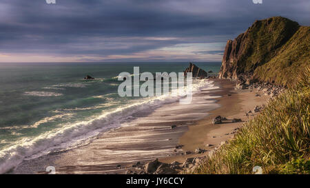 Ocean surf crashing onto wild deserted beach on New Zealand's South Island west coast, creating foam and backwash. - Stock Photo