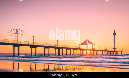 People walking along Brighton Beach jetty at sunset, South Australia - Stock Photo