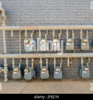 An array of natural gas meters metering gas usage by individual consumers behind a building in a strip mall. Norman, - Stock Photo