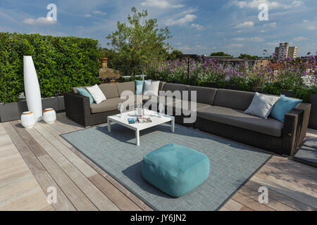 Luxurious roof terrace in London with hardwood timber decking, contemporary planters with lush planting and modern - Stock Photo