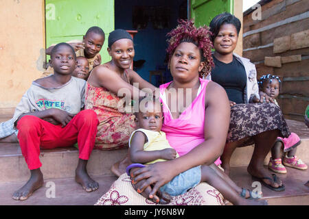 Lugazi, Uganda. June 13 2017. A group of smiling African women and children sitting together on stairs in front - Stock Photo