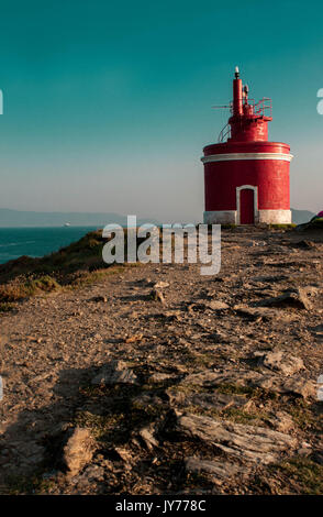 Lighthouse on top of the rocks with the sea and blue sky background in Cabo Home Galicia Spain - Stock Photo