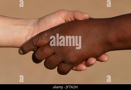 Handshake with white and black hands, District Omaruru, Namibia - Stock Photo