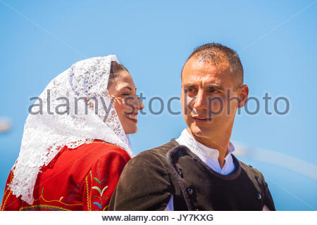 Portrait of a young couple riding on horseback together wearing traditional costume in the parade of the Cavalcata - Stock Photo