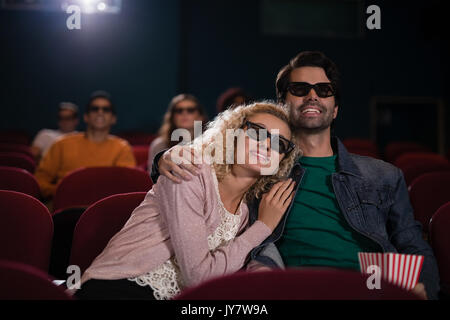 Happy couple watching movie in theatre - Stock Photo