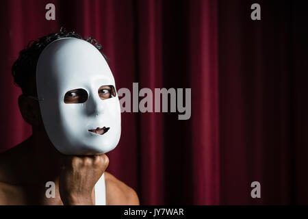 Portrait of artist wearing white mask on his face in stage - Stock Photo