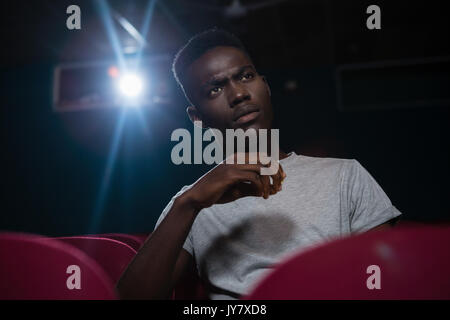 Concentrated man watching movie in theatre - Stock Photo