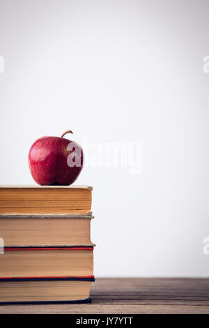 Close up of apple on books at table against wall - Stock Photo