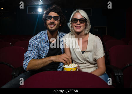 Happy couple having popcorn while watching movie in theatre - Stock Photo