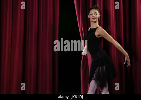 Ballerina performing ballet dance on stage in theatre - Stock Photo