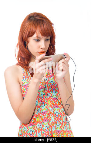 Girl concentrating on using her cellphone with a headset. Watching digital media. Redhead woman is wearing a colorful - Stock Photo