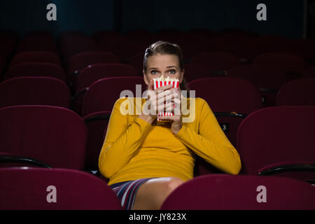 Woman scared while watching movie in theatre - Stock Photo