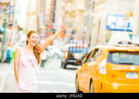 A young woman hailing a yellow taxi cab while walking on a street in New York city - Stock Photo