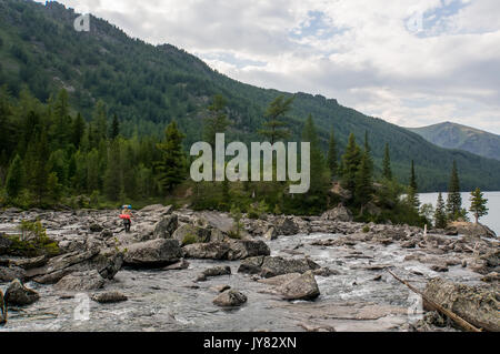 The tourist goes over the rocks on the shore of the lake. Altay Russia. Tourist pedestrian into the noise on the - Stock Photo