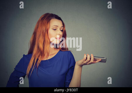 Frustrated annoyed upset woman with mobile phone standing by gray wall background - Stock Photo