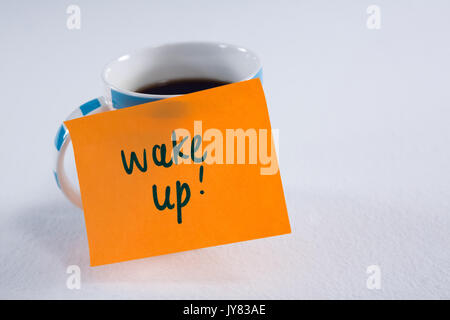 Close-up of black coffee with wake up message on white background - Stock Photo