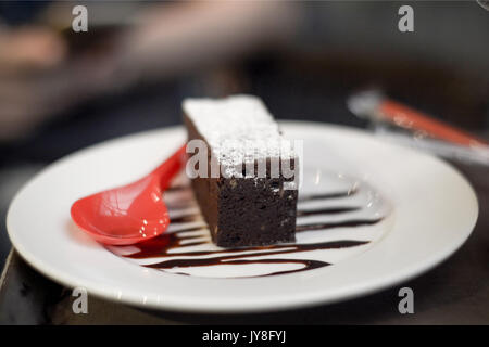 Brownies topped with chocolate with red spoon on the dish - Stock Photo
