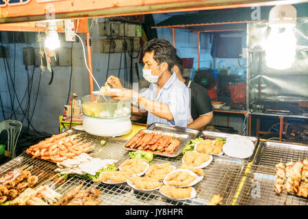 Ko Pha Ngan, Thailand - March 16, 2017. A man preparing some street food. - Stock Photo