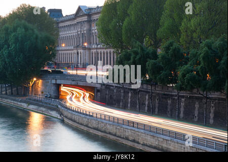 Car light trails at a tunnel exit on the river Seine borders in  - Stock Photo