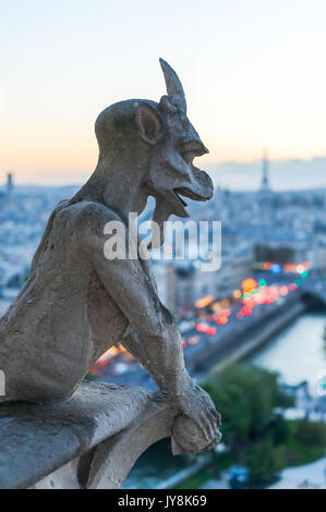 Gargoyle watching Eiffel tower and Paris at dusk - Stock Photo