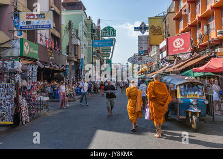 Two Buddhist monks among the crowd of foreigners, food vendors and neon signs at  Khao San Road in Bangkok, Thailand - Stock Photo