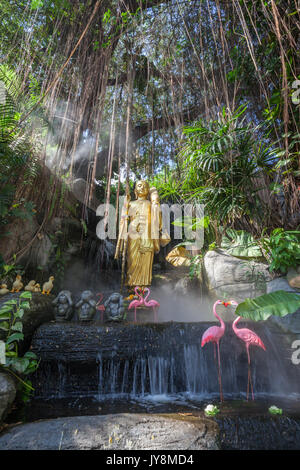 Golden Buddha statue in the tropical garden with waterfall in Wat Saket Golden Mountain Temple, Bangkok, Thailand - Stock Photo