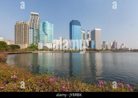 Benjakiti Park in Bangkok, Thailand skyline with Lake Ratchada, bougainvilleas and skyscrapers - Stock Photo