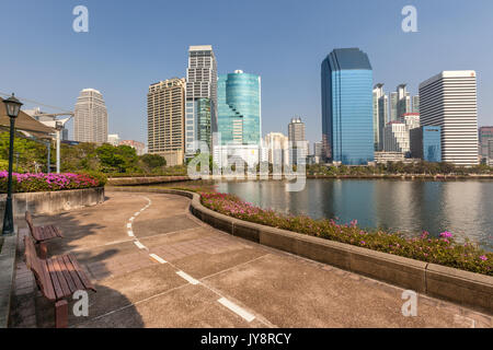 Benjakiti Park in Bangkok, Thailand skyline with jogging path around Lake Ratchada, bougainvilleas and skyscrapers - Stock Photo