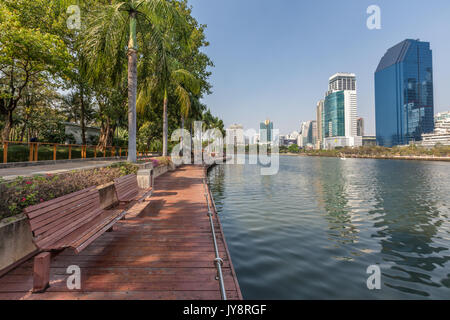 Benjakiti Park in Bangkok, Thailand skyline with the wooden boardwalk in front the Lake Ratchada and skyscrapers - Stock Photo